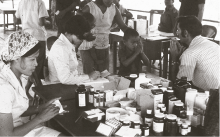 "AFRIMS Captain Michael ""Mike"" Benenson (future USAMC director)  returns a ""wai"" while the study team prepares medications in the 1973 malaria drug prophylaxis study. (Photograph courtesy of Dr. Michael Benenson)"