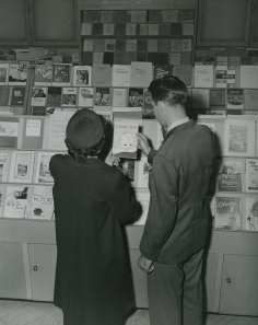 A couple looks at Infant Care pamphlet at GPO Bookstore: GPO Archives.