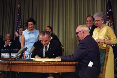 President Lyndon Johnson signs the Medicare Bill. President Harry S. Truman is seated next to him. Others looking on include Lady Bird Johnson, Vice President Hubert Humphrey, and Bess Truman. July 30, 1965. Photo courtesy of Lyndon B. Johnson Presidential Library, U.S. National Archives