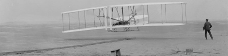 The iconic first flight of the Wright brothers in their 1903 Wright Flyer (Credit: NPS Wright Brothers National Memorial)