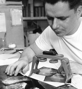Photo intelligence 3rd Class Charles R. Pearson uses his stereoscopic equipment to analyze an aerial image of an enemy site in Vietnam.