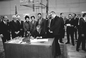 President Lyndon B. Johnson signs the Higher Education Act. Lady Bird Johnson, Congressman Jake Pickle, and others look on. LBJ Library photo by Frank Wolfe